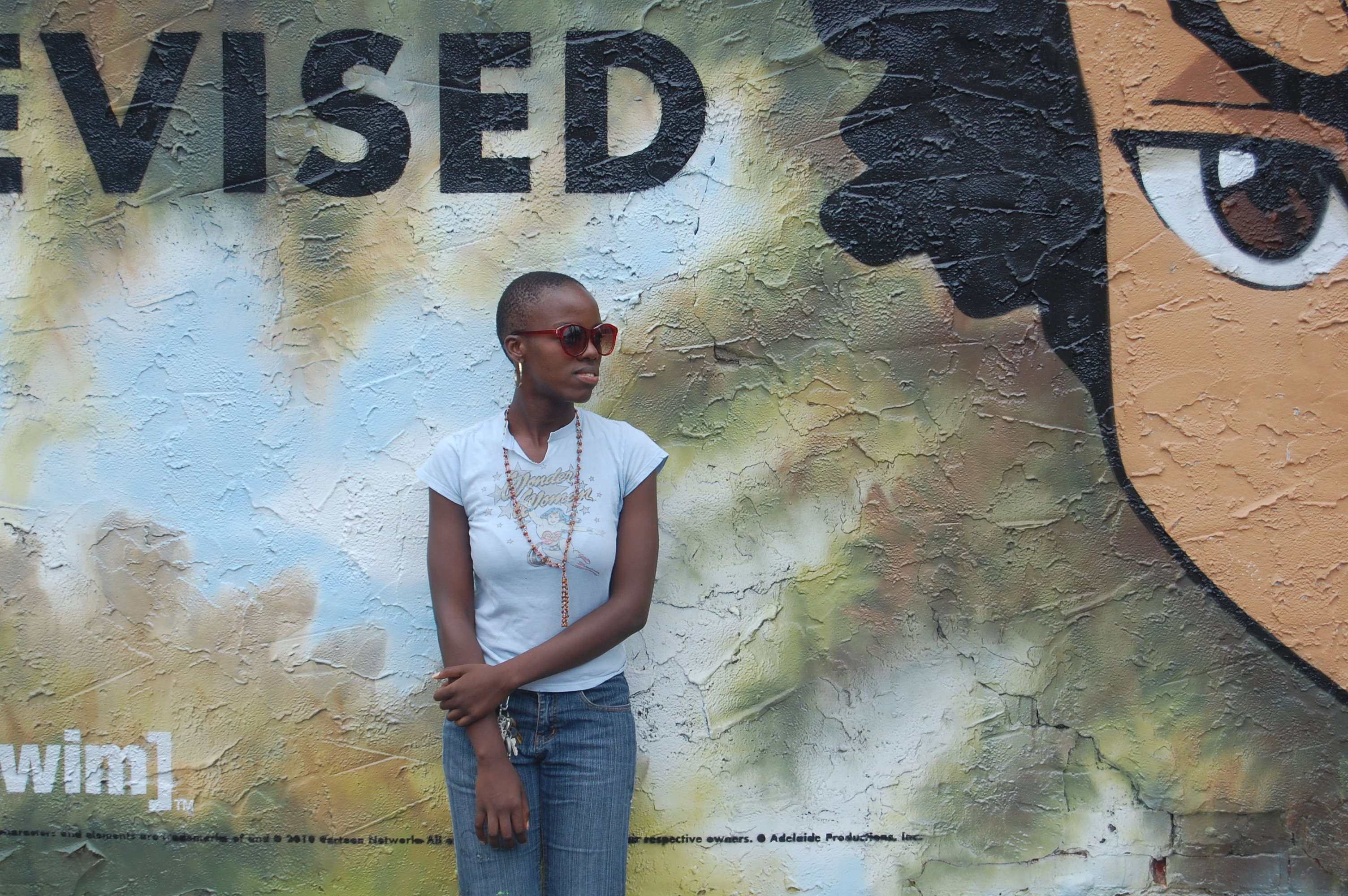 Dark skinned black girl in front of Ad for the Boondocks TV show with Huey's Eye in the frame.